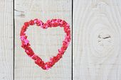 Mini paper hearts in the shape of a larger heart on a rustic wooden table. Perfect for Love and Valentines Day concepts. Horizontal format.