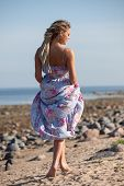 picture of dreadlock  - Happy young woman with dreadlocks walking along the seashore - JPG