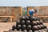 Child climbing on a stack of cannon balls in El Morro
