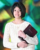 A pretty young tween happily carrying her Bible before a large, stained glass window.