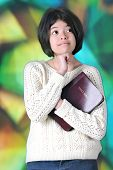 A pretty tween girl thinking while holding her Bible before a large, stained glass window.