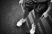 Lower part young man holding skipping rope