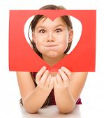 Little girl is looking through heart template, Valentine concept, isolated over white