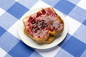 Fresh, hot toast spread with grape jelly sits during mealtime to be consumed.