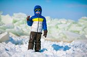 Cute little boy outdoors standing on winter beach