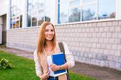 Student Standing On Building Background And Smiling