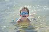 Cute little boy swimming in a shallow water