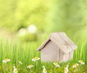 Kraft paper house on green grass in field