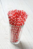 Closeup of a glass filled with red and white striped drinking straws on the rustic white wood table. Vertical format with copy space.