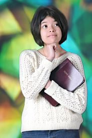 foto of tween  - A pretty tween girl thinking while holding her Bible before a large - JPG