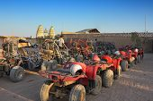 stock photo of four-wheel drive  - ATV and buggy safari in the parking lot in desert with blue sky - JPG