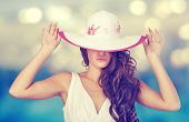 stock photo of beach hat  - Elegant woman in a white hat on the beach - JPG