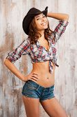 foto of young woman posing the camera  - Beautiful young woman in cowboy hat holding hand on hip and looking at camera while standing against the wooden background - JPG
