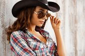 stock photo of cowgirls  - Beautiful young cowgirl adjusting her eyewear and looking at camera while standing against the wooden background - JPG