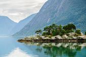foto of fjord  - Small rocky and pine island with mountains background at norwegian fjord - JPG