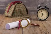 picture of private investigator  - Wrapped paper sheets and magnifying glass on Old Wooden table - JPG