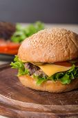 picture of beef-burger  - Closeup of classic burger made from beef and fresh vegetables on wooden background - JPG