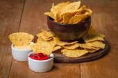 picture of nachos  - Mexican nacho chips and cheese and salsa dip in bowl on wooden background