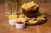 stock photo of nachos  - Mexican nacho chips cheese and salsa dip in bowl and tequila on wooden background