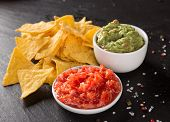 image of nachos  - Green Guacamole with nachos and avocado on stone background - JPG