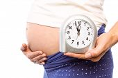 stock photo of bump  - Pregnant woman showing clock and bump on white background - JPG