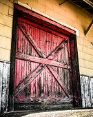 stock photo of loading dock  - Large red door on a loading dock that is aged and weathered - JPG
