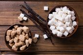 foto of sugar cube  - White and brown sugar cubes in bowsl and vanilla beans on dark wooden background - JPG