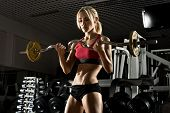 stock photo of execution  - beautiful girl bodybuilder execute exercise with weight in dark gym - JPG