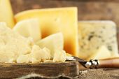 stock photo of cutting board  - Different sort of cheese on wooden cutting board - JPG