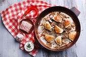 stock photo of fried onion  - Fried dumplings with onion and bacon in frying pan - JPG
