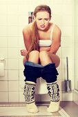 picture of peeing  - Young woman sitting on a toilet - JPG
