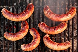 picture of braai  - BBQ Bratwurst Spicy Browned Sausages On The Hot Grill Top View - JPG