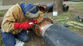 foto of pipe-welding  - Welder worker wearing protective clothing and safety gear welding two big pipes - JPG