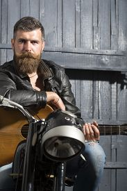 stock photo of moustache  - Attractive unshaven musical man with beard and handlebar moustache in leather jacket sitting on motorcycle with acoustic guitar in garage on wooden wall background copyspace vertical picture - JPG