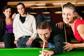 stock photo of snooker  - Group of four friends in a billiard hall playing snooker - JPG