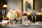 picture of wedding table decor  - table setting for a wedding or dinner event very shallow depth of field with the focus on the flowers blurry background and blank name cards - JPG