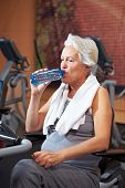 Senior Woman Drinking Water In Gym