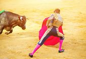 Постер, плакат: Traditional corrida bullfighting in Spain Matador in Ring with Bull Spanish torero fighting on a