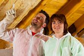 stock photo of glass-wool  - Couple installing thermal insulation thru glass wool on their roof - JPG