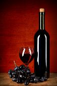 Bottle Of Wine, Glass And Grapes Over Red  Grunge Background