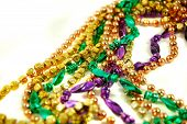 stock photo of mardi-gras  - strands of mardi gras beads isolated on a white background - JPG