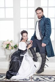 foto of pompous  - Beautiful couple woman and man in medieval clothes in the room - JPG