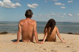 image of naturist  - a Naked family sitting on the beach - JPG