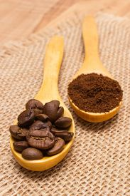 pic of coffee grounds  - Coffee beans and ground coffee on wooden spoon lying on jute canvas coffee grains - JPG
