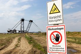 stock photo of open-pit mine  - Warning sign near a giant mining excavator at a open pit mine near Cologne - JPG