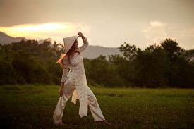 picture of long distance  - slim blonde girl closeup in Vietnamese white long dress and hat looks into distance on field against sky at sunset - JPG