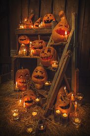 stock photo of scary haunted  - Scary Jack O Lantern halloween pumpkins against wooden wall in darkness - JPG