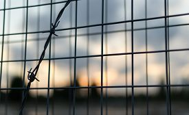 foto of safety barrier  - Strong barbed wire fence and wire mesh barrier with blurred clouds as a background - JPG