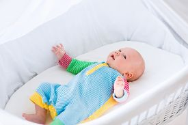pic of bassinet  - Newborn baby boy playing in bed on a sunny morning - JPG