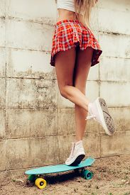 pic of up-skirt  - Close up of a young girl with sporty ass in a red tartan mini skirt stand on blue penny skateboard trying to climb over the fence of a tropical garden - JPG